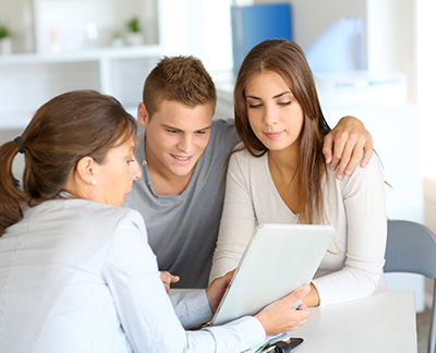 young couple reviewing mortgage options with adviser